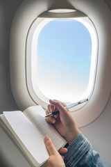 Woman writing on blank notebook while travelling on plane.