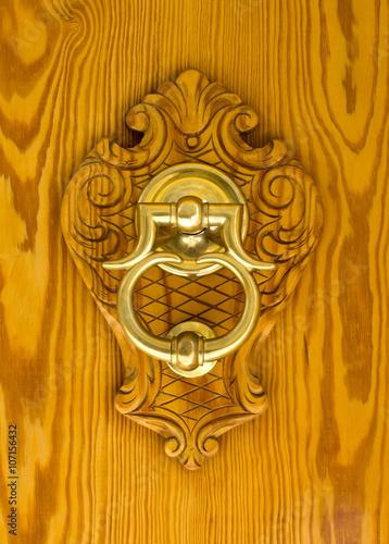 Modern Spanish Brass Door Knocker Mounted On Carving Set On A Pine Front  Door.