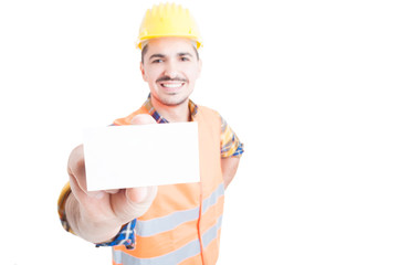 Cheerful constructor showing blank visit card in close-up