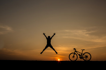 silhouette of man and bicycle on sunset sky
