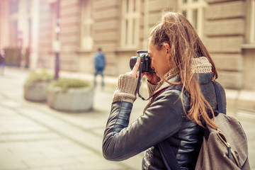 Pretty young female tourist photographer taking pictures in the city