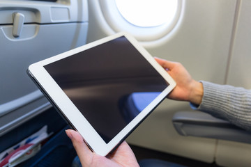 Woman use of tablet pc inside air plane