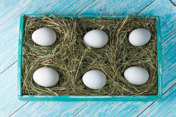 Chicken eggs. Chicken eggs in the nests of straw on a decorative wooden tray.