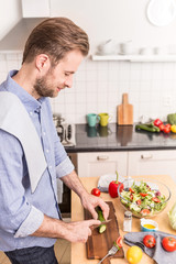 Happy smiling man chopping vegetables to make salad