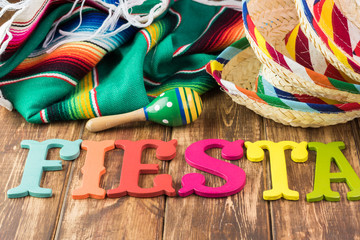 Mexican fiesta table decoration with colorful fiesta maracas, sombreros, fiesta wooden letters.