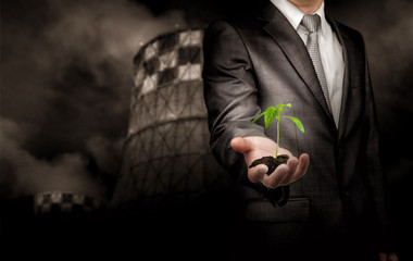 Sprout growing on the ground in hand of businessman standing over thermal power plant background