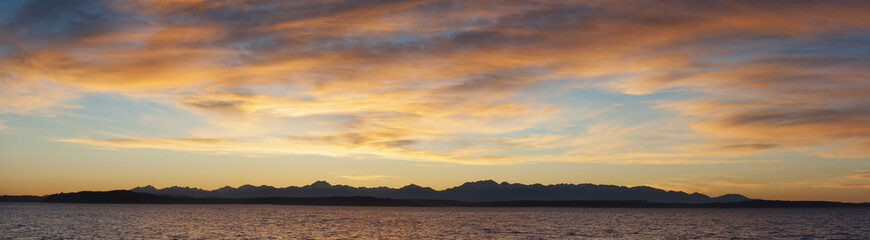 Olympic Mountains Panorama. Panoramic view of the Olympic Mountain range seen from the Seattle waterfront during a dramatic springtime sunset.