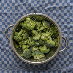 Fresh organic broccoli in a metal sieve on a blue checkered kitc