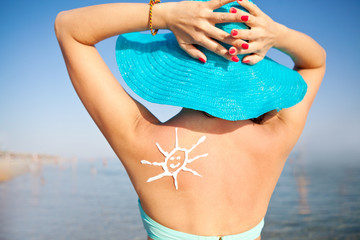 Girl in a hat with sunscreen on his shoulder