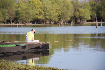 landscape - a fisherman in a boat by the lake