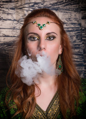 close-up portrait of a elegant young redhead woman, with oriental make-up and shawl over her head bright red lips, smokes a hookah, let the smoke out of his mouth