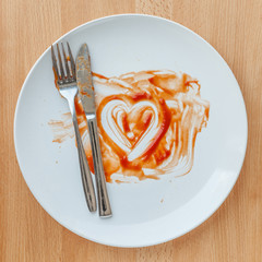 Knife and fork over in finish plate and heart shape ketchup, con