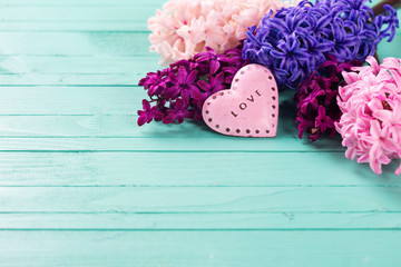 Fresh hyacinths  and  decorative heart  on  wooden background.