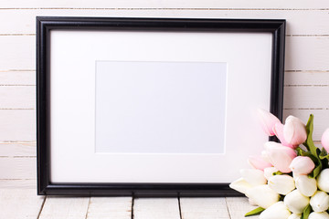 Empty frame and  pink flowers  on white wooden background.