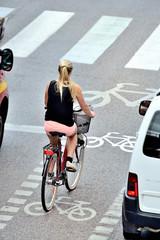 Fototapete - Woman on bike waiting for green light in bike lane
