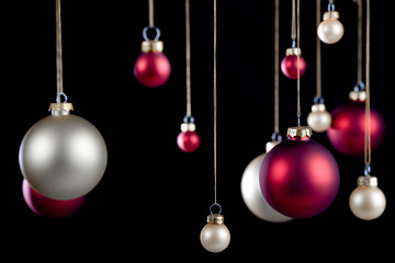 red and silver hanging christmas ornaments isolated on black