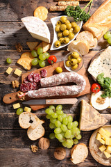 assortement of cheese with grape,bread, and salami