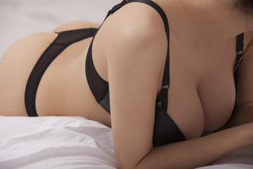 Sexy Woman in black lingerie lying on bed. Erotic pose
