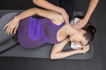 Trainer massaging pregnant woman