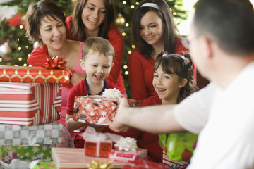 A group of people, parents and children, family exchanging presents on Christmas morning.