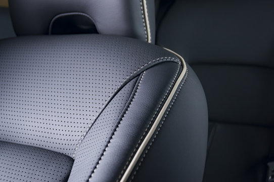 Part of  leather car seat with the unfocused car interior on the background