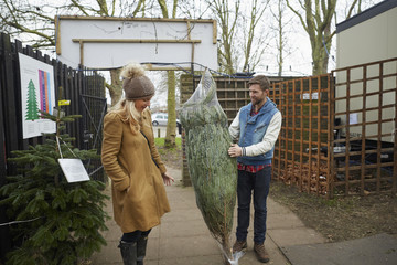 A member of staff carrying a traditional pine tree, Christmas tree talking to a woman client.