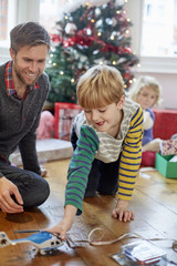 A man and two children finding and unwrapping presents on Christmas day.