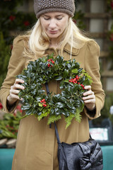A woman carrying a decorated wreath of holly and evergreen leaves.