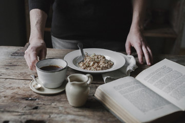 A person at a table with a cup of coffee, bowl of muesli and an open book.