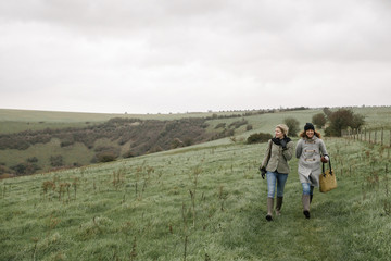 Two women walking on a country path across grassland.