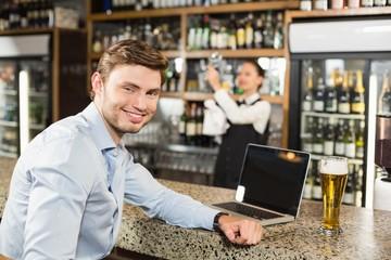 Man smiling at camera in a bar
