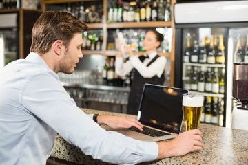 Man working on laptop with beer in hand