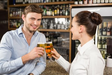 Man and barmaid toasting with beers