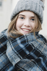 A young girl in a tartan plaid shawl and woolly hat outdoors in the winter.