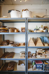 Shelves in a wood turner's workshop and a display of smooth wooden blocks and round platters and bowls.
