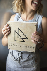 A woman in a blue apron holding her business sign, a square piece of wood with a triangle logo.