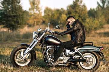 young brutal man in a black jacket and glasses sits near a motorcycle.