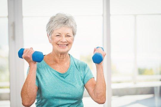 Portrait of smiling senior woman holding dumbbell