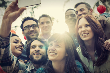 A group of friends gathering to take a group selfie.