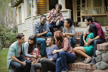 A group of friends sitting on the steps of a house porch, talking and laughing.