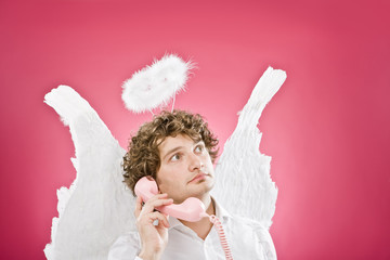 smiling blonde angel talking on the phone isolated on pink