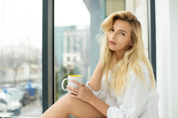 Beautiful blonde woman next to a window