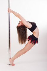Young sexy pole dancer on white background