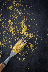 fork with remains of couscous on black stone