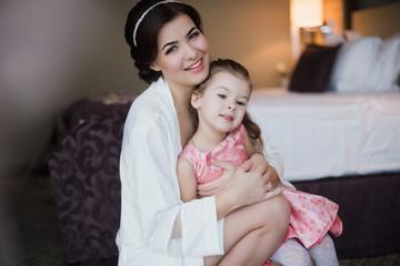 Beautiful mother hugs daughter in the bedroom, motherhood, family
