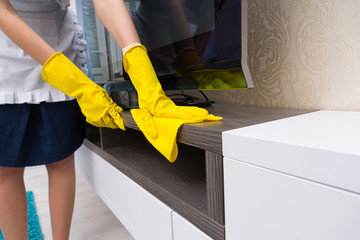 Housekeeper cleaning and dusting a TV cabinet