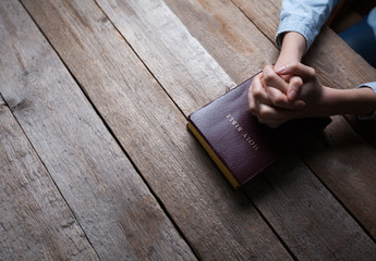 hands praying with a bible in a dark over wooden table Wall mural
