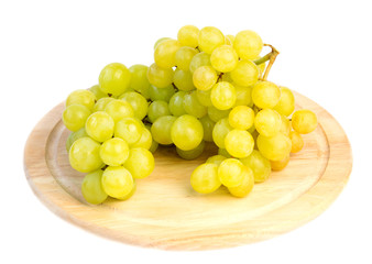 Fresh grapes on a wooden board, isolated on white background