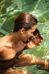femme dans l'eau transparente touchant ses cheveux