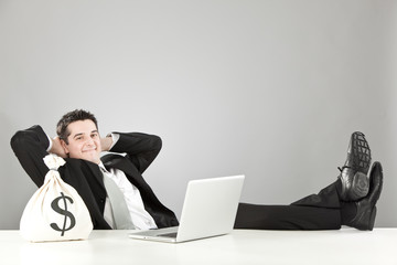 relaxed happy businessman with money bag and laptop isolated on grey